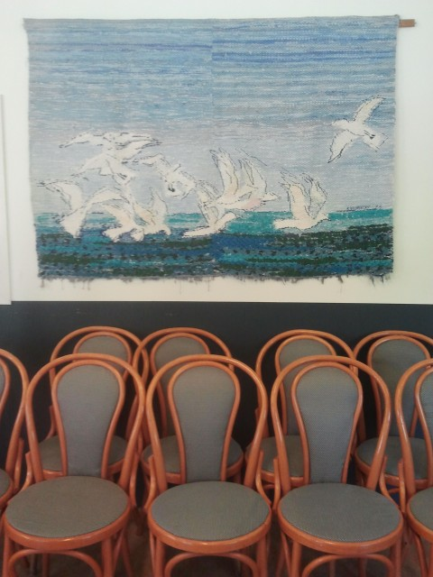 Weaving of seagulls hanging above rows of chairs at Verdandi women's center, Fittja